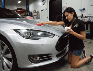 A lady waxing a white vehicle with the best car wax for white cars