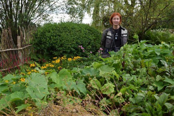 Rothaarige Motorradfahrerin vor Hochbeeten im Roji-Garten in Bartschendorf im Havelland