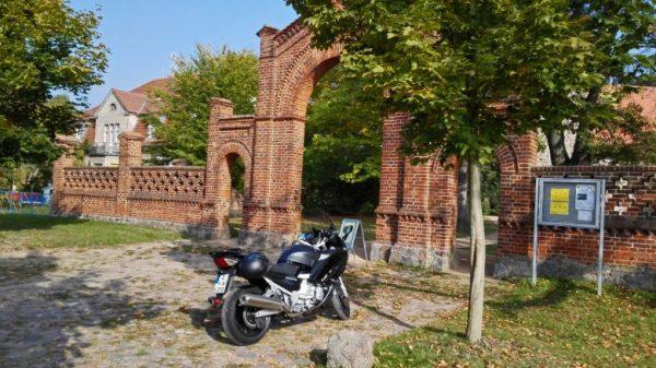 Einer der ungewöhnlichen Picknickplätze: Yamaha FJR 1300 vor dem gemauerten Eingang der Dorfkirche von Radensleben, Lkr. Neuruppin in Brandenburg