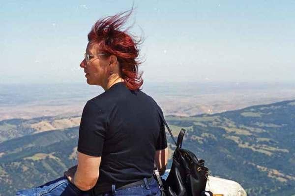 Rothaarige Motorradfahrerin auf dem Mt. Diablo in Kalifornien mit Panorama über das Land