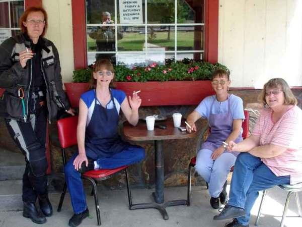 Rothaarige Motorradfahrerin bei der Zigarettenpause mit drei anderen Damen in Paradise Post, Clark Fork Valley, Montana