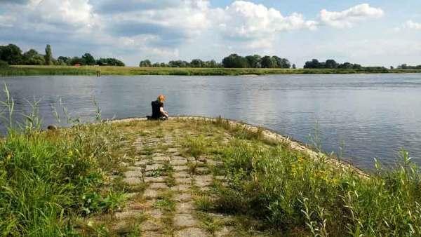 Rothaarige Motorradfahrerin am Oderstrand bei Lebus beim Picknick am Fluss bei einer Motorradtour Spree Oderland