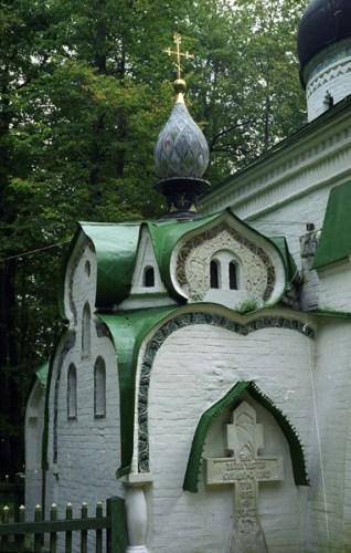 Bild Orthodoxe Kirche Abramzewo mit weissen Ziegelmauern und gruenem Dach und Gedenkkreuz im Vordergrund