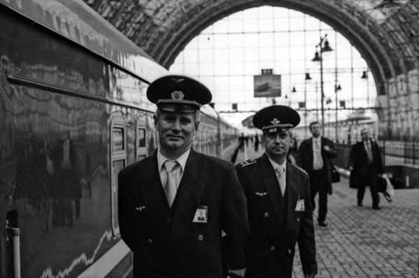Zwei Eisenbahnschaffner am Bahnsteig eines Bahnhofs in Moskau vor fahrbereitem Zug stehend