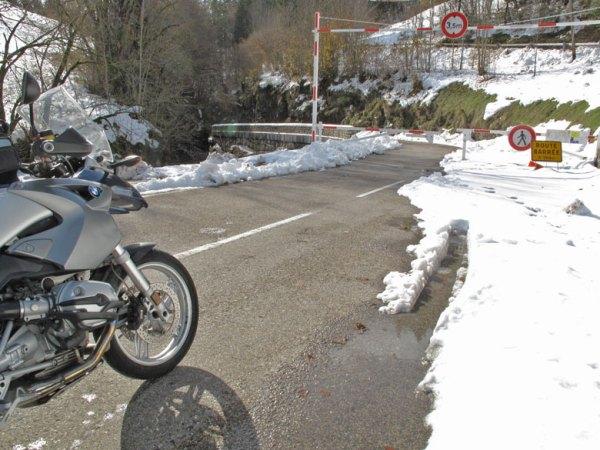 Motorrad BMW R 1200 GS mit Schnee am Strassenrand vor einer Strassensperre bei einer Motorradtour durch den winterlichen Vercors