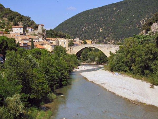 Flüsschen Eygues und Bogenbrücke mit Ortsansicht von Nyons in Südfrankreich mit den Gorges de trente pas im Hintergrund