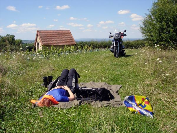 Rothaarige Motorradfahrerin auf einer Wiese liegend mitr BMW R 1200 GS im Hintergrund
