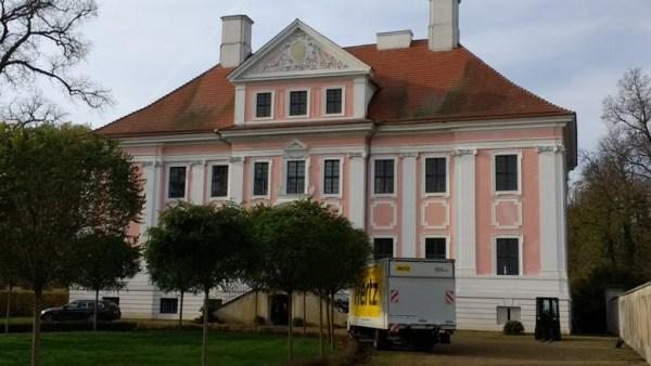 Vorderansicht von Schloss Gross Rietz in der Niederlausitz mit Möbelwagen beim Einzug der neuen Mieter