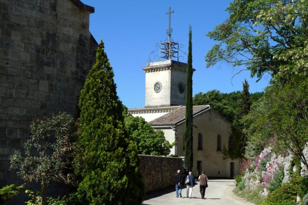 Kloster Aiguebelle in der Drôme Provençale zwischen Montélimar und Taulignon mit dem Klostergebäude, einem Glockenturm und blühenden Büschen rundum