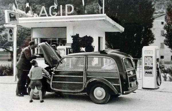 """Bild von einer AGIP-Tankstelle in Italien 1954 mit einem FIAT 500 Kombi """"Giardiniera"""". Tankwart, Faher und ein kleiner Junge in Lederhose stehen vor der geöffneten Motorhaube"""
