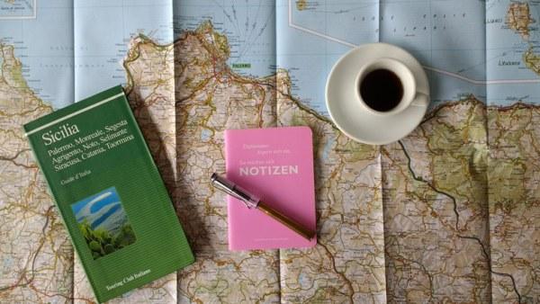 Motorradtour planen mit Landkarte und Reiseführer von Sizilien, eine Tasse Espresso und ein Notizbuch