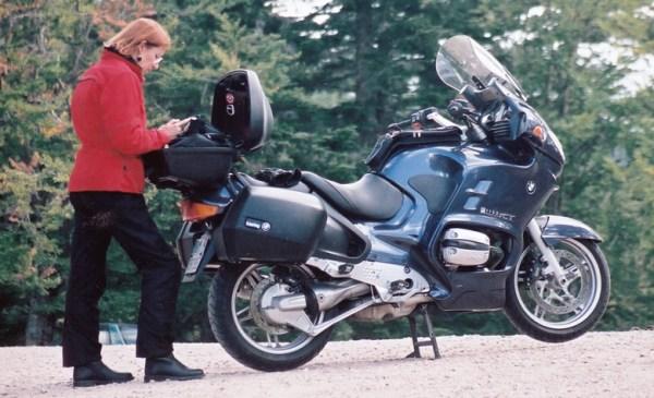 Blaues Motorrad BMW R 1150 RT mit Heck- und Seitenkoffern und einer rothaarigen Motorradfahrerin in roter Jacke als Beispiel für Smart Packing für die grosse Motorradtour