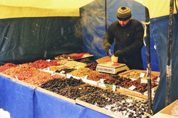 Usbekischer Nussverkäufer auf winterlichem Markt in Moskau mit allerlei Nüssen und Trockenfrüchten aus seiner Heimat im Angebot