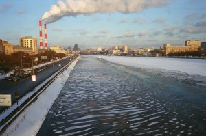 Bild von einem Wärmekraftwerk an der Moskwa mit rot-weißen Schornsteinen, die weiße Wolken ausstoßen