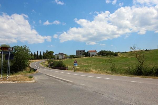 Via Cassia zwischen Viterbo und Orvieto mit Strassenschildern und Häusern im Hintergrund