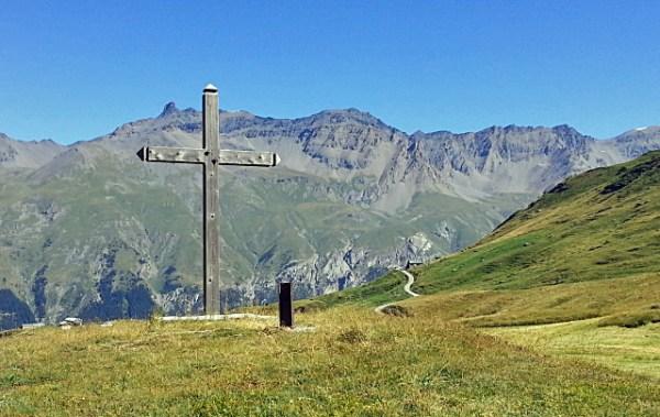 Gipfelkreuz auf dem Mont Cenis mit grünen Almwiesen und einer hohen Bergkette im Hintergrund macht Lust auf Alpenpässe in Savoyen