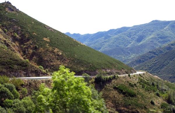 Einsame Strasse in der Ardèche mit einer Serpentine durch die Hügel mit Buschwerk