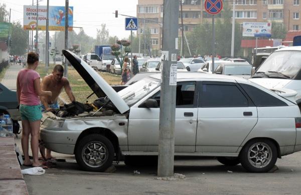 Zwei Männer bei der Autoreparatur in Moskau auf dem Gehsteig mit einem Auto und offener Motorhaube