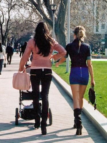 Zwei langbeinige junge Frauen in Russland bei einem Frühlingsspaziergang, von denen eine einen Kinderwagen schiebt.