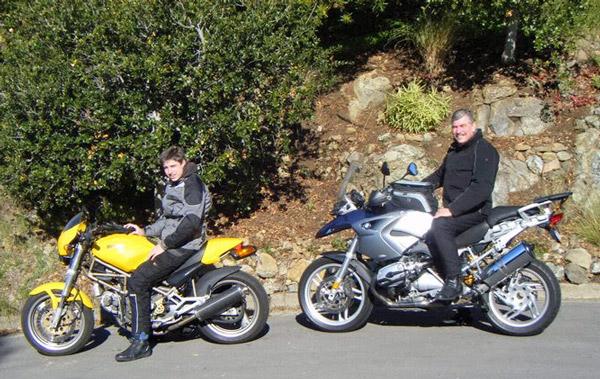 Mann auf einer blauen BMW R 1200 GS und sein Sohn auf einer gelben Ducati Monster 750 vor der Ausfahrt