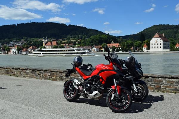 Ducati Multistrada 1200 S und einer Yamaha FJR 1300 am Donauufer bei Obernzell mit einem Passagierschiff im Hintergrund