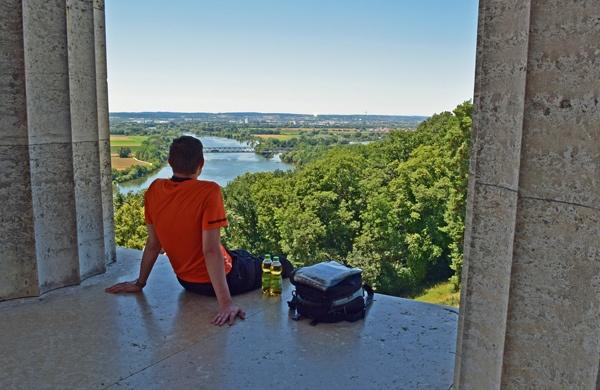 Pause auf der Süd-Nord-Motorradstrecke durch Deutschland: Panoramablick von der Walhalla auf die Donau mit einem jungen Motorradfahrer im orange T-Shirt und einem Tankrucksack