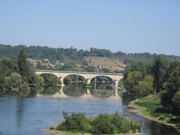 Dordogne Übergang bei Ste-Foy-la-Grande in Südwestfrankreich mit einer Flussinsel im Vordergrund, einer Steinbrücke im Mittelgrund und dem Dorf im Hintergrund