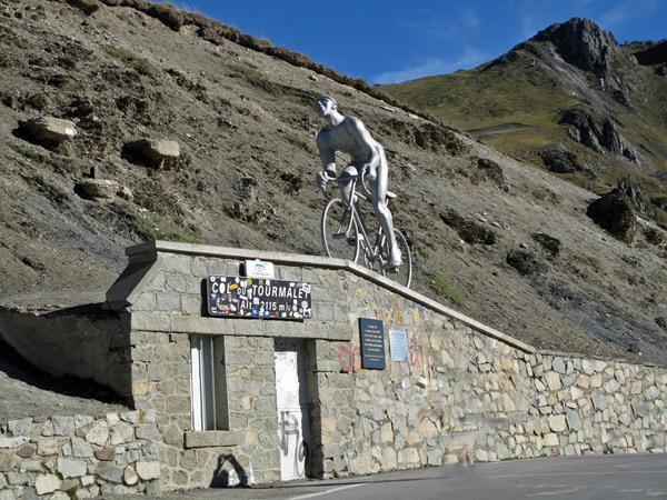 Passhöhe des Col du Tourmalet in den französischen Pyrenäen mit dem Höhenschild und einem Denkmal aus Metall, das einen Radrennfahrer darstellt, gesehen bei einer Motorradtour Südwestfrankreich Teil 2