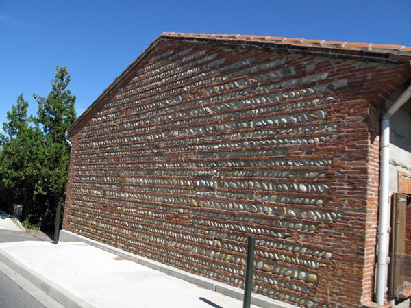 Steinmauerwerk aus Natur- und Ziegelsteinen bei einem Haus im Pyrenäenvorland südlich von Toulouse
