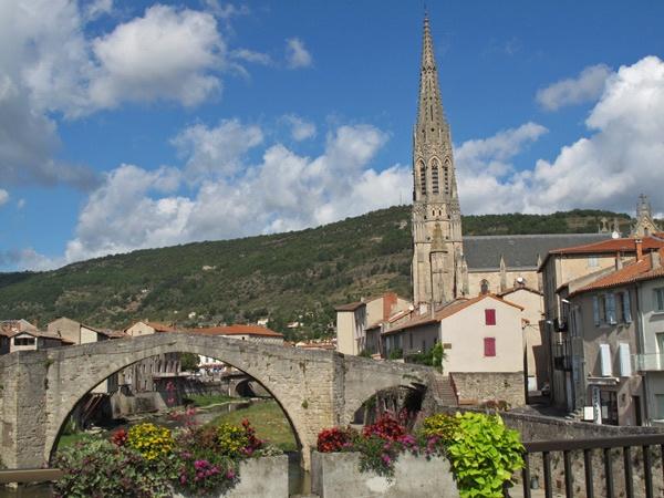 St-Affrique im Département Aveyron vom Fluss aus mit steinerner Brücke, Kirche, Häusern am Flussufer und buntem Blumenschmuck
