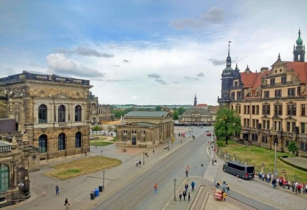 Semperoper und Grünes Gewölbe in Dresden im Bild mit Blick auf die Dresdner Neustadt am Horizont und abendlichen Spaziergängern auf der Straße