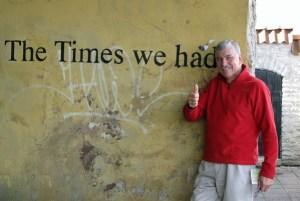 """Mann im roten Pullover vor einer gelblich verschmierten Hauswand mit der schwarzen Aufschrift """"The Times we had"""" als Symbol für die Motorrad-Tourenerfahrungen eines langen Sommers"""