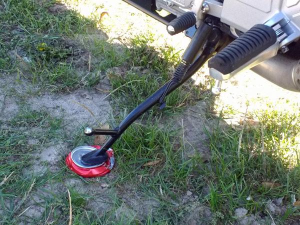 Motorrad-Seitenständer auf einer plattgedrückten Getränkedose, damit der Seitenständer nicht in den weichen Boden einsinkt
