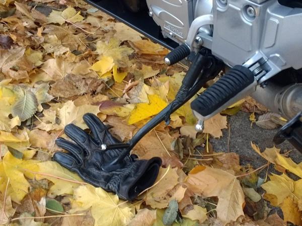 Untergelegter Handschuh als Stützplatte verhindert das Einsinken des Motorrad-Seitenständers in den aufgeweichten oder sandigen Boden.
