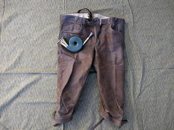 Hirschlederne Kniebundhose für die Jagd mit einem Taschenhorn, auf einer Zeltplane liegend