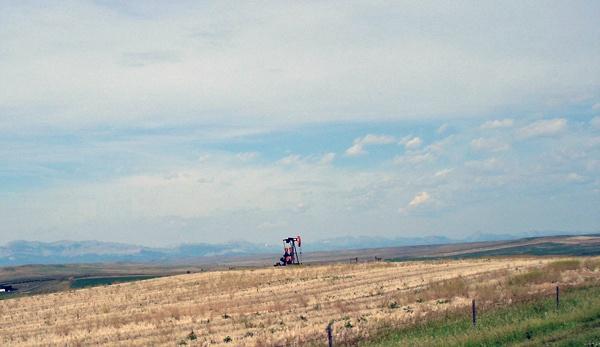 Ölpumpe auf einem Feld in Montana an der U.S. Road 89 mit den Rocky Mountains im Hintergrund