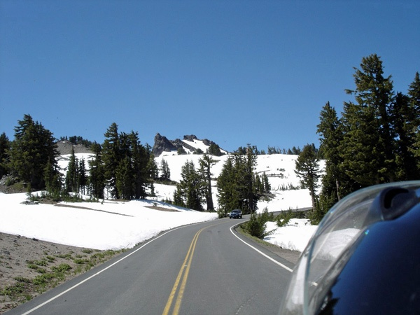 Auffahrt zum Crater Lake in Oregon von einem Motorrad aus in schneebedeckter Landschaft mit entgegenkommenden Fahrzeugen