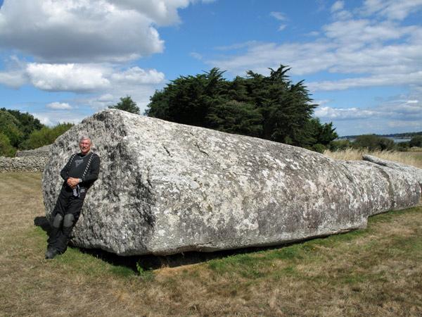 Liegender Grand Menhir von Locmariaquer an der bretonischen Atlantikküste mit einem Motorradfahrer in schwarzer Kombi