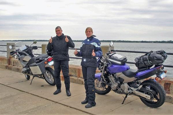 Motorradfahrer und blonde Motorradfahrerin mit ihren Maschinen am Atlantik in Charleston, SC am Ende ihrer USA-Motorradtour vom Pazifik zum Atlantik
