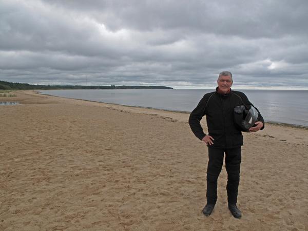 Motorradfahrer in schwarzer Kombi mit Helm unter dem Arm am Golf von Riga