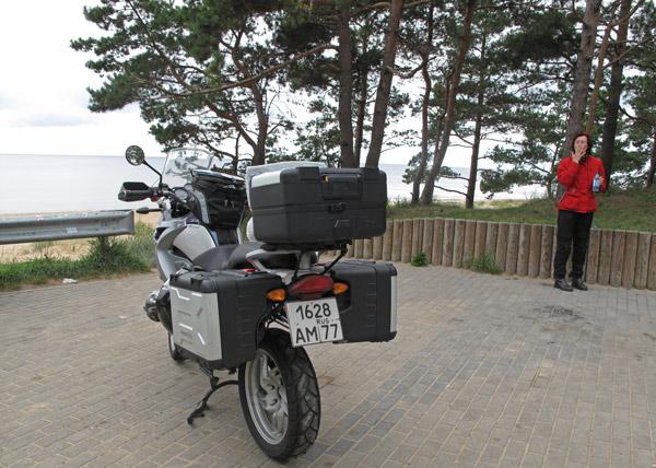 Rothaarige Motorradfahrerin mit einer BMW R 1200 GS bei einer Zigarettenpause am Golf von Riga