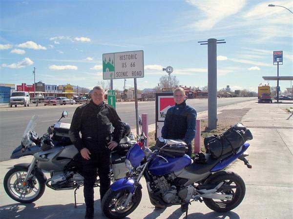 Motorradfahrer und blonde Motorradfahrerin bei der Abfahrt in Seligman, AZ auf der Route 66 bei einer USA-Motorradtour vom Pazifik zum Atlantik