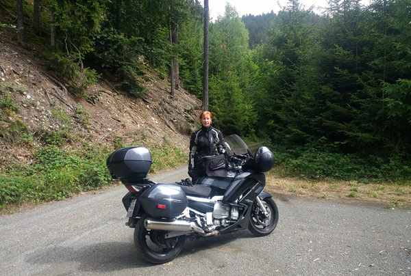 Rothaarige Motorradfahrerin mit Maschine auf dem Waldweg an der Ziemestalbrücke bei einer Motorradtour durch den Thüringer Wald
