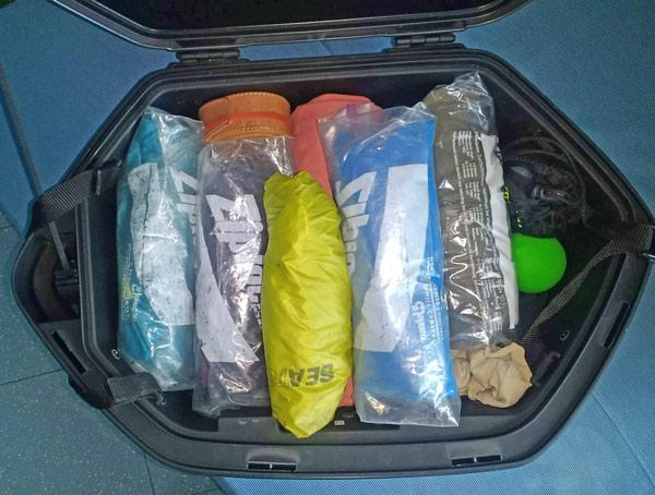 Gepackter Motorradkoffer mit zusammengerollter Wäsche als Beispiel für Smart Packing für die grosse Motorradtour
