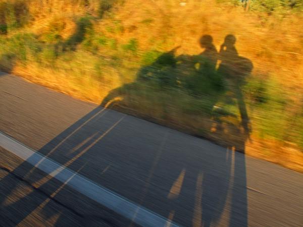Warum fahre ich Motorrad? Schattenbild eines Motorrades mit Fahrer und Sozia im Abendlicht