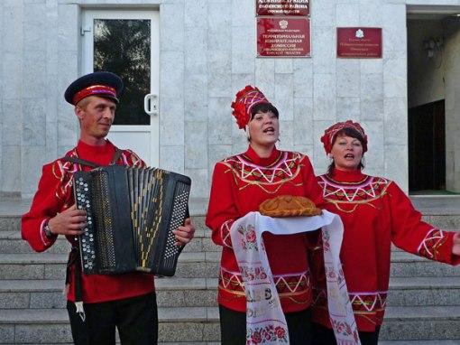 Begegnungen bei Motorradtouren: Russische Musikgruppe in roter Tracht bei der Begrüßung