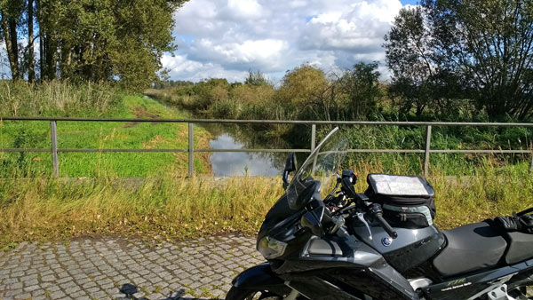 Schwarzes Motorrad auf einer Bruecke uebereinen Kanal im Rhinluch (Brandenburg)