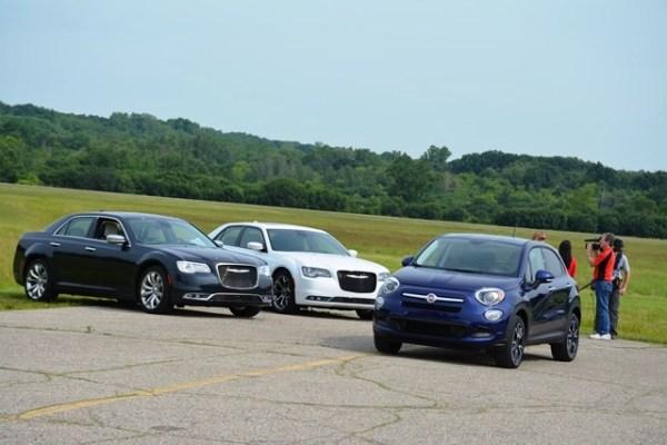 Listo para salir hacia la pista, el nuevo Fiat 500X pasa frente a una pareja de Chrysler 300.