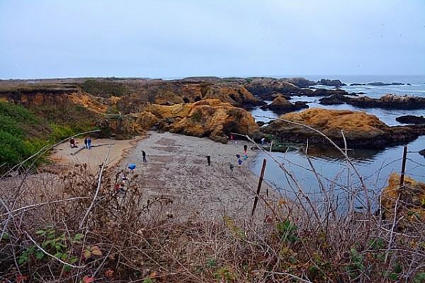Gente explorando la peculiar orilla de Glass Beach