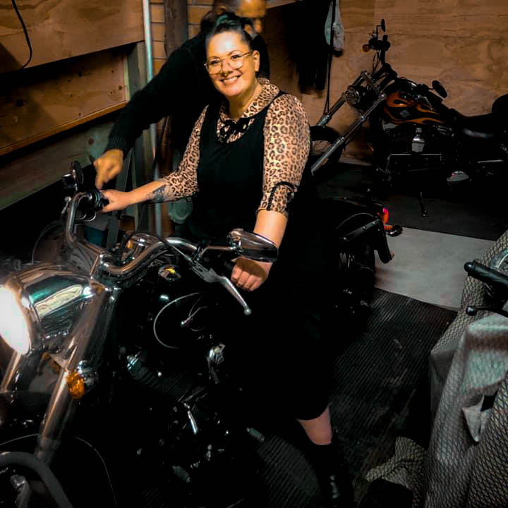 Smiling Woman sitting on her motorcycle in garage sharing tips on what to pack when motorcycle camping